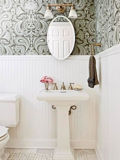 powder room with light gray & chocolate brown damask wallpaper, chair rail & beadboard, glossy white pedestal sink, marble tiles with marble basket weave inset tiles, oval pivot mirror and brass towel holder & frosted clear glass double sconce...