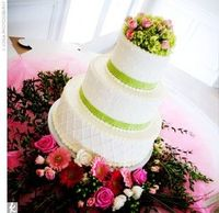 A three-tier white cake decorated with polka dots, crisscross lattice frosting, and green ribbon. A bundle of green hydrangeas and pink roses topped the confection.