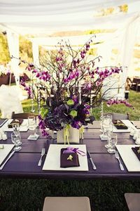 Very pretty dark table with square plates and floral centerpiece