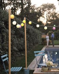 Use wooden poles, anchored in flower buckets, filled with garden gravel to string outdoor lights.