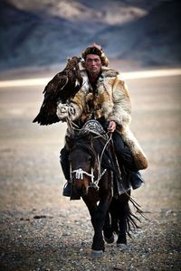 A hunter in Mongolia, riding a horse, armed with a Golden Eagle.